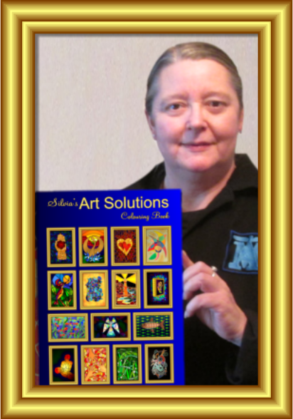Silvia Hartmann holding up a copy of the Art Solutions Colouring Book