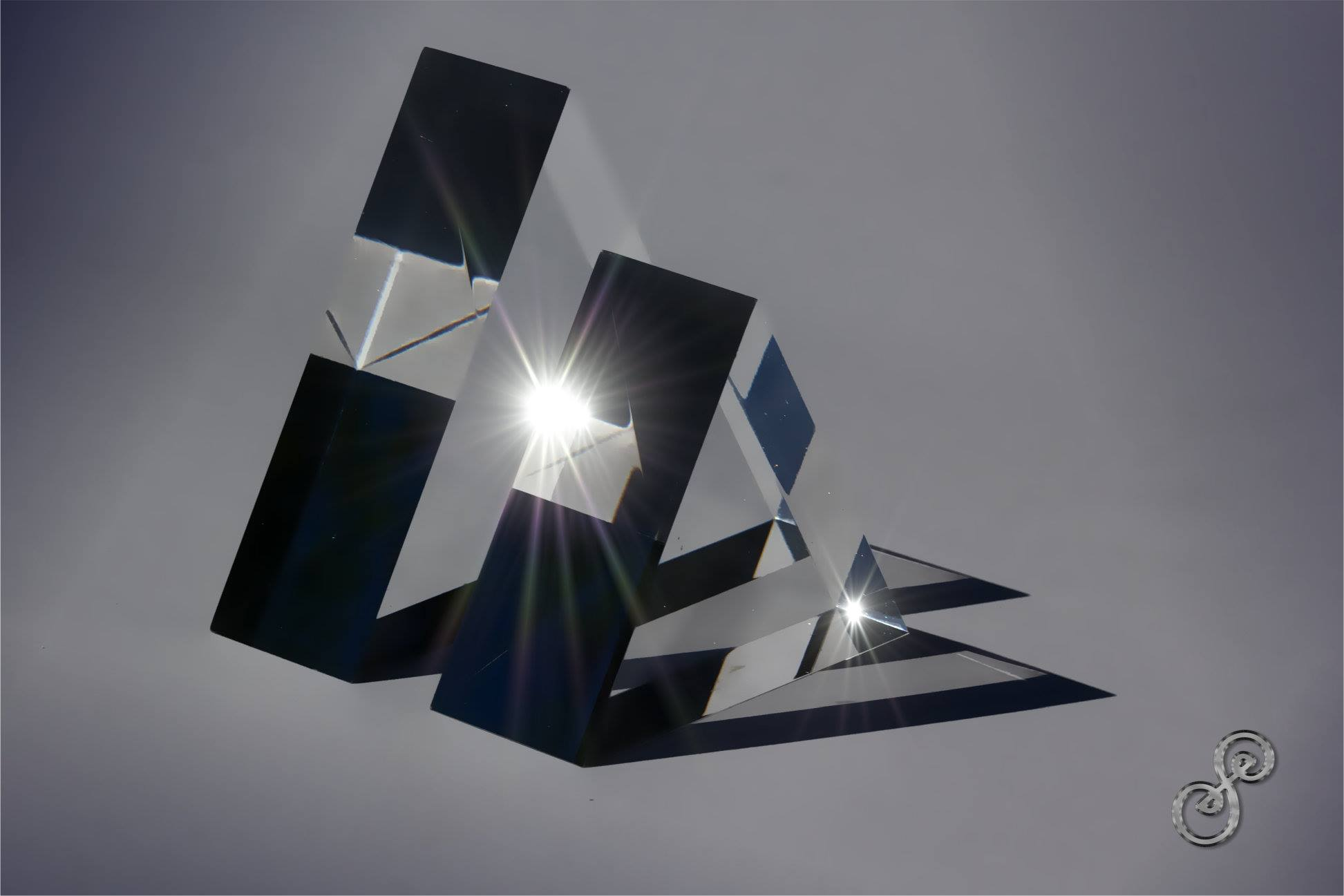 I Have Your Back - Two Prisms, a bigger one and a smaller one, standing behind one another in near monochrome with light