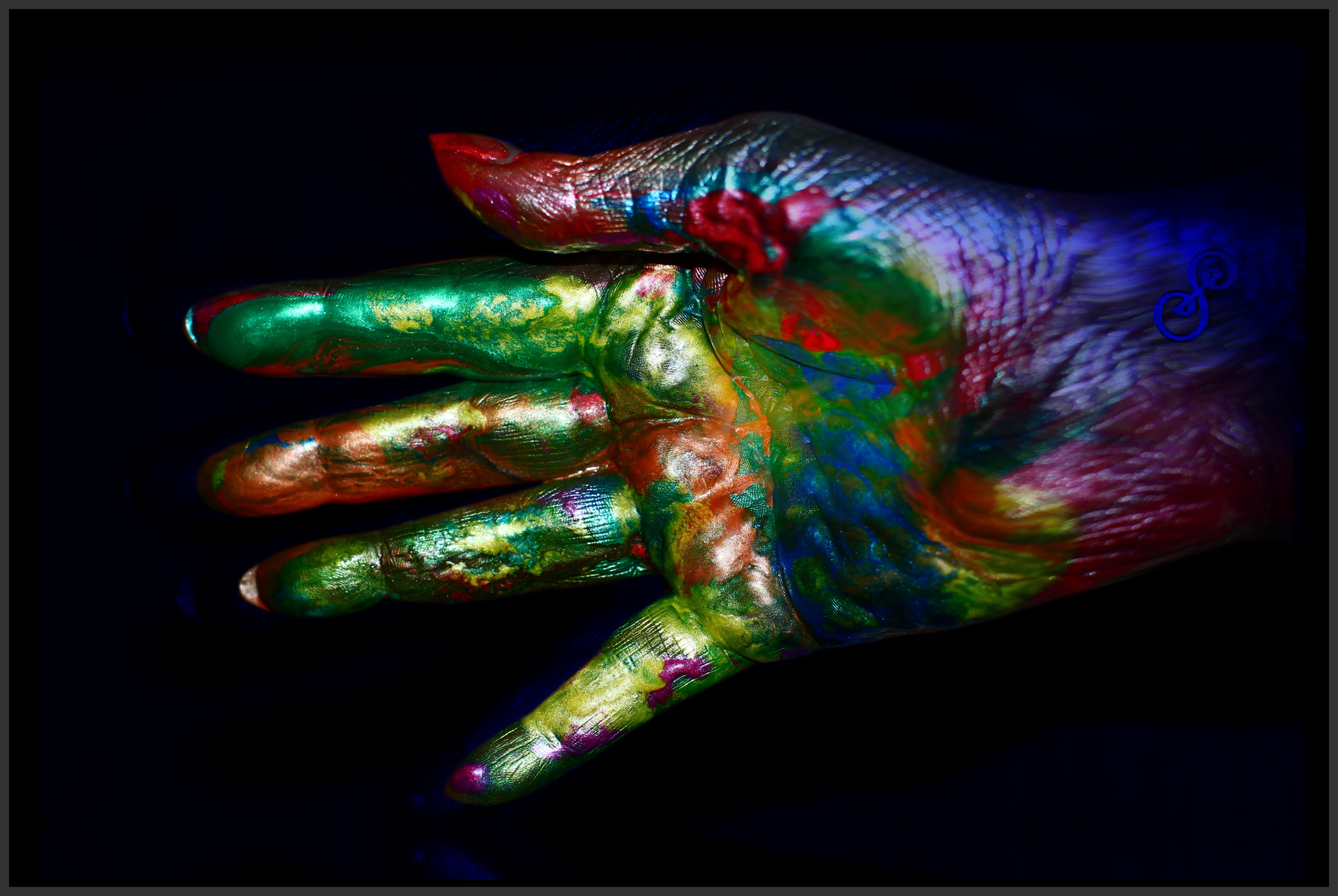 Hand covered in multi-coloured paint reaching out for a hand shake photograph on black background