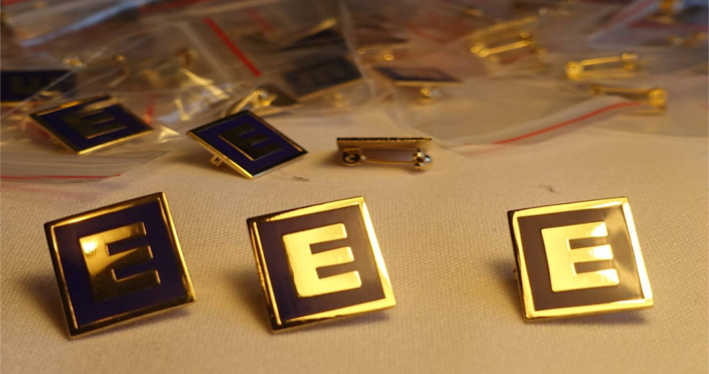 E Logo gold plated blue enamelled pin badges