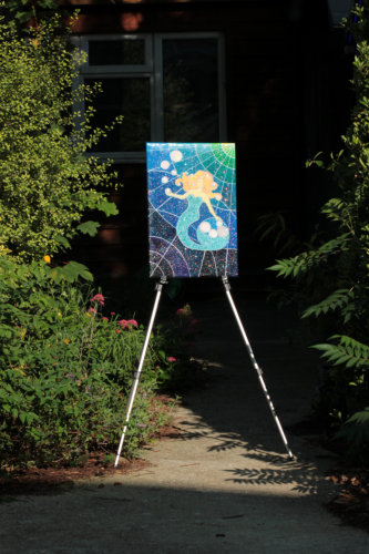 Sparkly mermaid energy painting on an easel in the garden